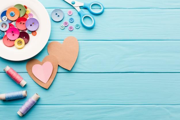 Mise à plat de coeurs en papier pour la saint valentin avec des fournitures de couture Photo gratuit