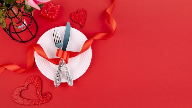 Mise à Plat Des Couverts Sur Une Plaque Avec Ruban Et Coeurs Photo gratuit