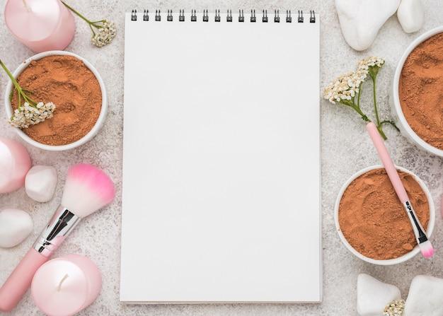 Mise à Plat Du Cahier Avec De La Poudre Dans Des Bols Et Des Pinceaux Photo gratuit