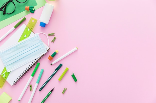 Mise à Plat Du Matériel De Retour à L'école Avec Des Masques Et Des Crayons Photo gratuit