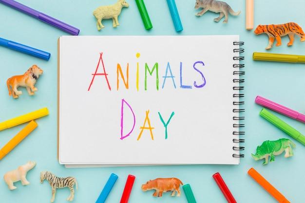 Mise à Plat De Figurines D'animaux Et D'écriture Colorée Sur Ordinateur Portable Pour La Journée Des Animaux Photo gratuit