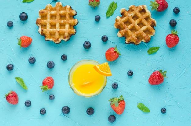 Mise à Plat. Gaufres, Jus D'orange, Fruits Rouges Et Feuilles De Menthe Sur La Surface Bleue Photo Premium
