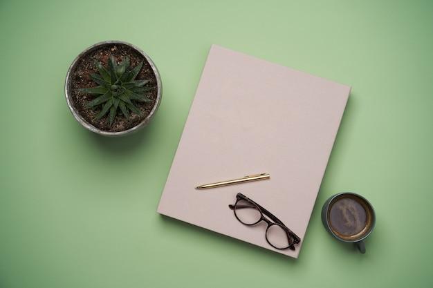 Mise à Plat Avec Livre, Tasse à Café, Lunettes De Lecture, Stylo Et Crayons Sur Vert Photo Premium