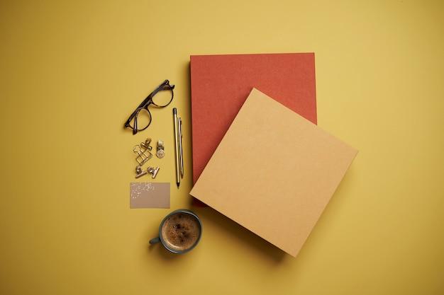Mise à Plat Avec Livres, Tasse à Café, Lunettes De Lecture, Stylo Et Crayons Sur Jaune. Photo Premium