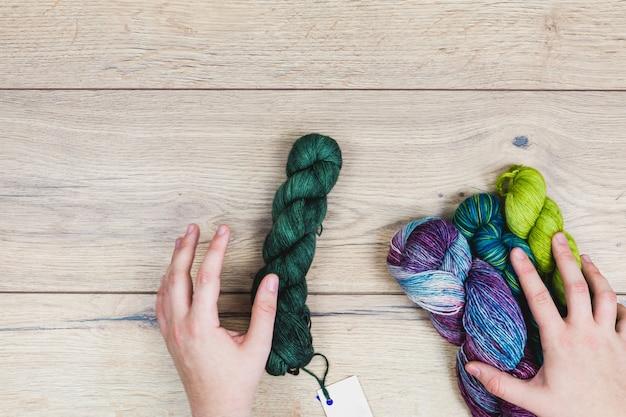 Mise à Plat De Mains Humaines Choisissant De Belles échevettes Dans Des Tons Violets Et Verts Avec étiquette Vierge Pour Maquette Sur Une Table En Bois Photo Premium