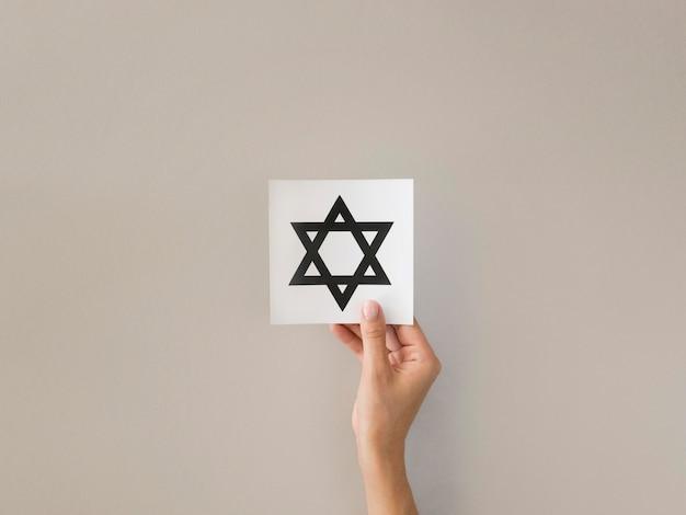 Mise à Plat Des Mains Tenant Le Symbole De L'étoile De David Photo gratuit