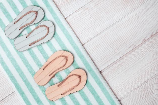 Mise à Plat D'une Miniature Composée D'un Salon De Plage Avec Des Chaussures D'été - Deux Paires De Tongs, Une Serviette En éponge Photo Premium