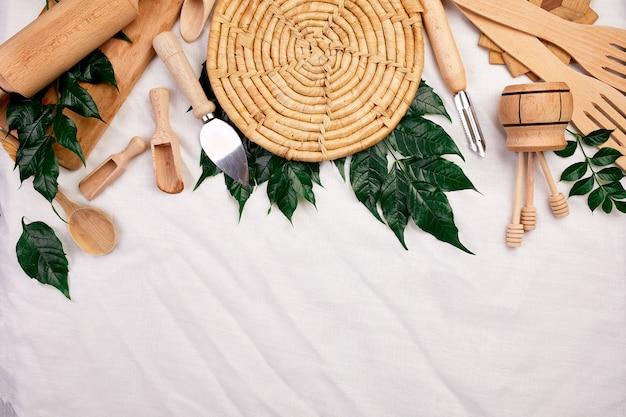 Mise à Plat Avec Des Ustensiles De Cuisine En Bois Avec Des Feuilles Vertes, Ustensiles De Cuisine Sur Textile Photo Premium