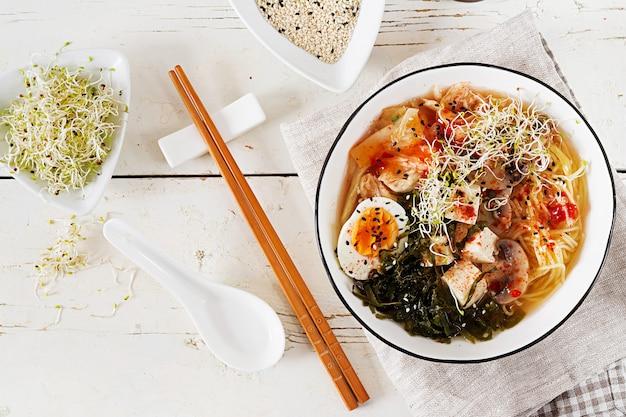Miso ramen nouilles asiatiques avec kimchi au chou, algues, œuf, champignons et tofu au fromage dans un bol sur une table en bois blanche. cuisine coréenne. vue de dessus. pose à plat Photo Premium