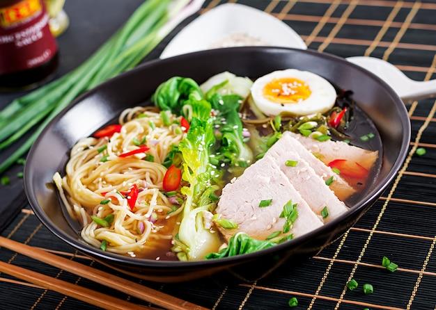 Miso ramen nouilles asiatiques avec oeuf, porc et chou pak choi dans un bol. cuisine japonaise. Photo Premium
