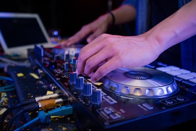 Mixage dj sur scène, disc jockey et mix de pistes sur contrôleur de mixage sonore, lecture de musique à une soirée dans une discothèque. Photo Premium