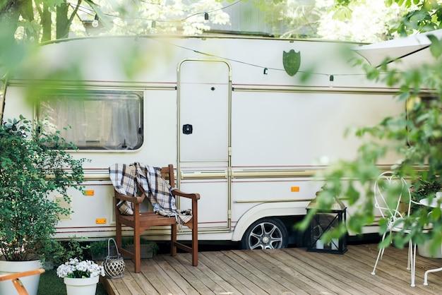 Mobil-home Van Avec Terrasse, Maison Sur Roues. Camping Caravane. Roulotte Sur Roues Dans Un Jardin Verdoyant. Bande Annonce Photo Premium