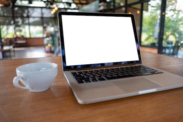Mock up à l'aide d'un ordinateur portable avec un ordinateur à écran blanc espace de travail moderne dans un café Photo Premium