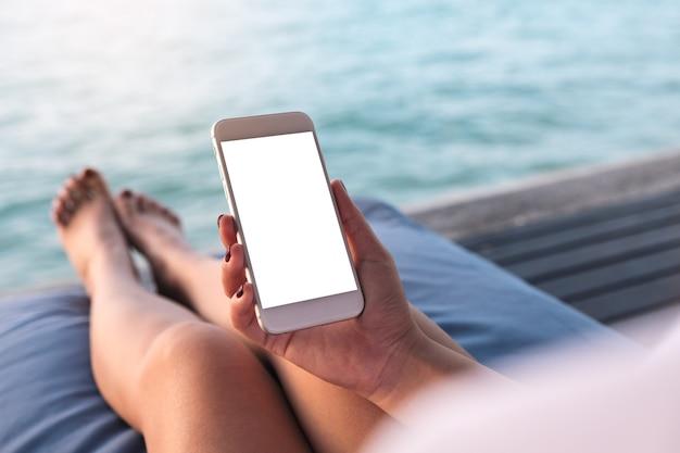 Mockup téléphone intelligent avec des personnes main au bord de la mer Photo Premium