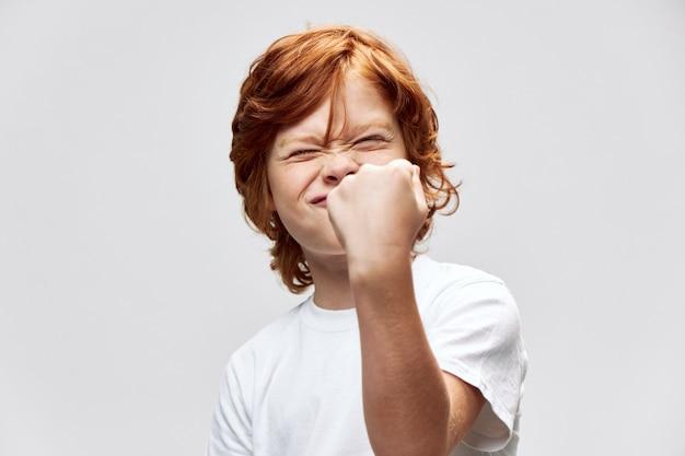 Mode émotionnel, Un Garçon Aux Yeux Plissés Montre Un Poing Et Un Enfant Obéissant Photo Premium