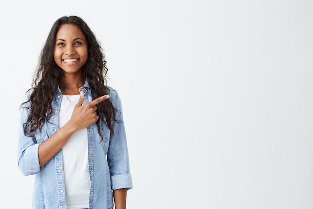 À La Mode émotionnelle Jeune Femme Afro-américaine Portant Une Chemise En Jean Pointant Son Index Sur Un Mur Blanc Blanc Derrière Elle, L'air Positif Et Heureux, Largement Souriant. Photo gratuit