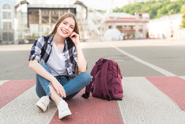 Mode femme souriante assise sur la route avec son sac à dos Photo gratuit