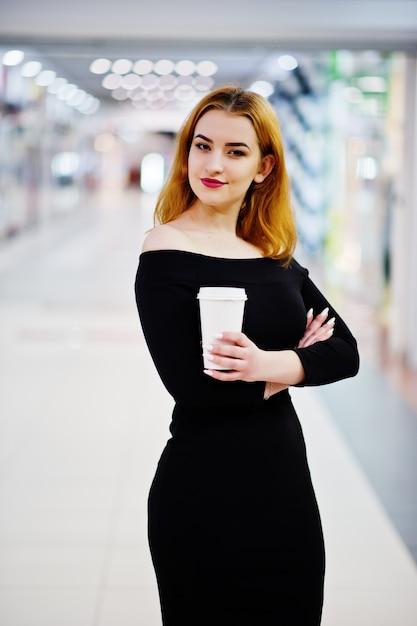 Mode fille aux cheveux rouge porter sur une robe noire avec lumineux faire tenue tasse à café au centre commercial Photo Premium