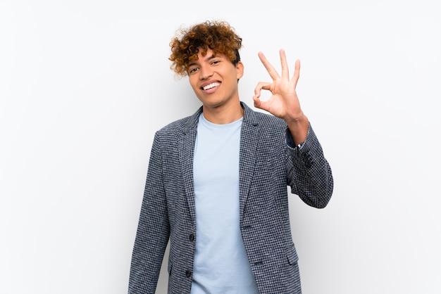 Mode homme afro-américain sur mur blanc isolé, montrant un signe ok avec les doigts Photo Premium