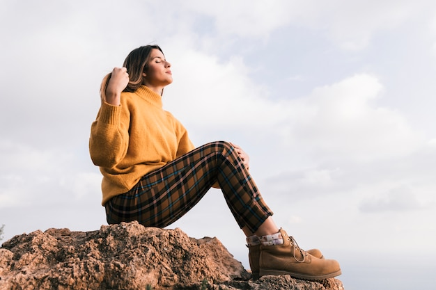 À la mode jeune femme assise sur le rocher, profitant de la nature dans le ciel Photo gratuit