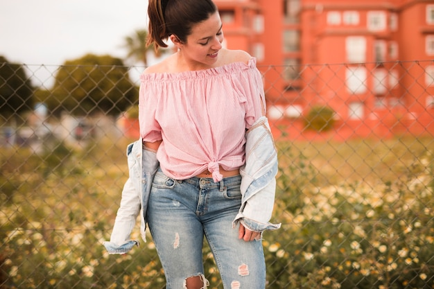 La mode jeune femme debout devant la clôture à la recherche de suite Photo gratuit