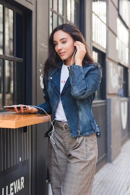 À la mode jeune femme écoutant de la musique sur des écouteurs via un téléphone mobile Photo gratuit