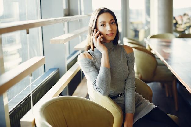 Mode jeune fille assise dans un café Photo gratuit
