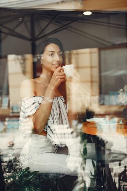 Mode jeune fille dans un café d'été Photo gratuit
