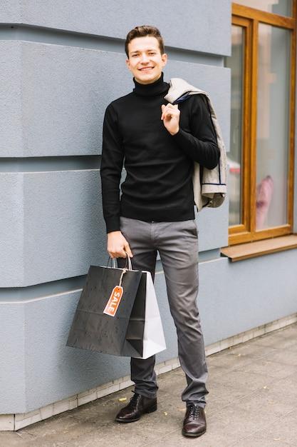 c63716afadc À la mode jeune homme avec des sacs à provisions tenant veste sur ...