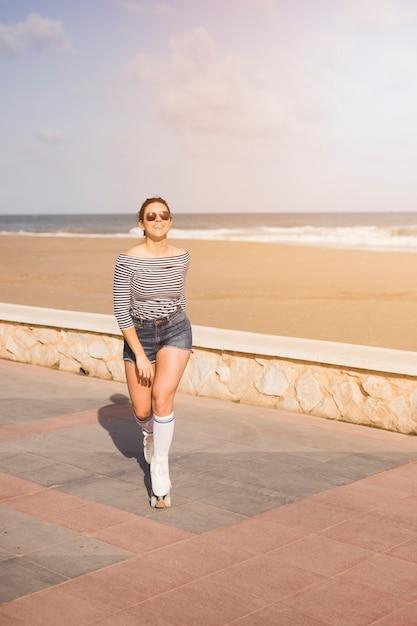 À la mode jeune patineuse marchant près de la plage Photo gratuit