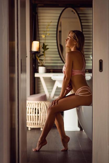À la mode mince belle jeune femme se prépare dans la salle de bain à la maison. figure féminine sportive en lingerie rose, style de vie de vanité. Photo Premium