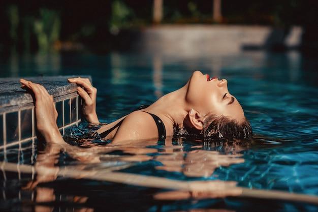 Mode en plein air belle femme aux cheveux blonds porte luxueux maillot de bain noir, posant dans la piscine. femme de luxe se trouve dans la piscine cristalline Photo Premium