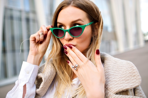 Mode En Plein Air Bouchent Le Portrait D'une Superbe Femme Blonde D'affaires, Souriant Et Regardant La Caméra, Manteau En Cachemire, Lunettes De Soleil Vintage Oeil De Chat, Bijoux, Couleurs Douces. Photo gratuit