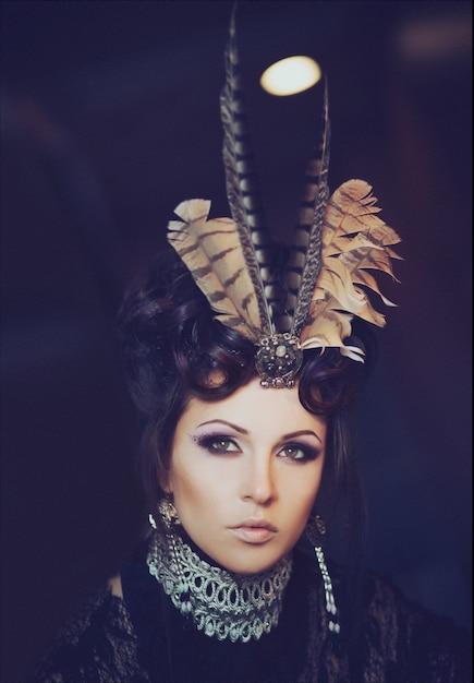 Mode portrait d'une belle brune vêtue d'une robe de dentelle noire. maquillage créatif et coiffure avec des plumes. halloween Photo Premium
