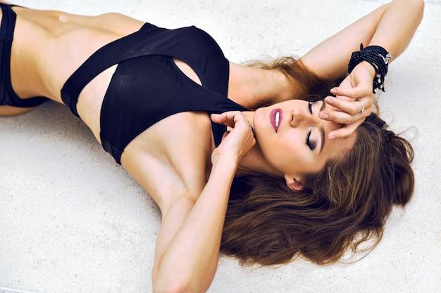Mode Portrait D'été D'une Superbe Femme Brune Allongée Sur Le Sol, Portant Un Bikini Minimaliste Inhabituel à La Mode Et Un Maquillage Lumineux Photo gratuit