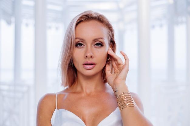 Mode Portrait De Femme Blonde Européenne En Soie Blanche Robe Romantique D'été Bracelet Doré Et Boucles D'oreilles Photo gratuit