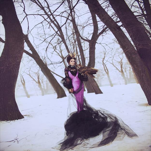 Mode portrait d'hiver d'une belle brune dans une longue robe lilas avec un hibou. coiffure créative et maquillage. halloween Photo Premium