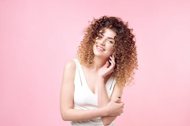 Mode portrait studio de belle femme souriante avec afro boucles coiffure isolé Photo Premium