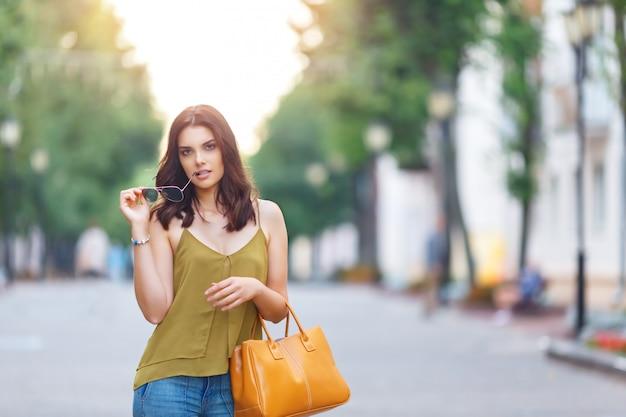 Mode portrait de ville de femme élégante hipster avec sac, tenue naturelle, maquillage, longs cheveux bruns, marcher seule le week-end, passer des vacances en europe Photo Premium