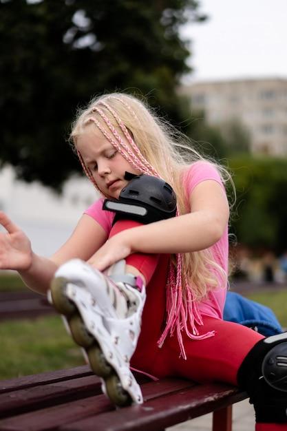 Mode de vie actif dans une ville moderne - une fille enfile des patins à roulettes dans le stade Photo Premium