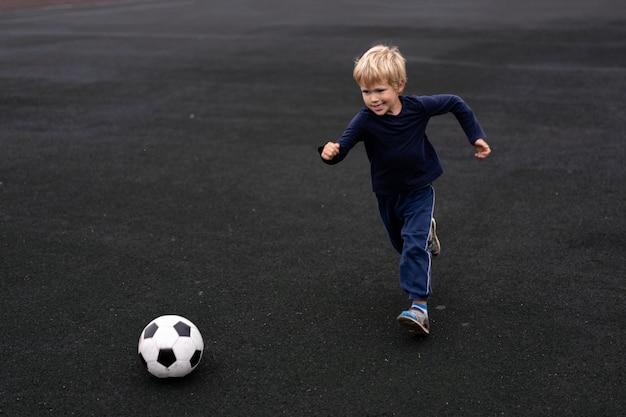 Mode de vie actif dans une ville moderne - petit garçon jouant avec un ballon de football dans le stade Photo Premium