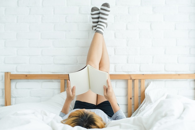 Mode de vie heureux jeune femme asiatique profitant de s'allonger sur le lit en lisant un livre plaisir en vêtements de loisirs Photo gratuit