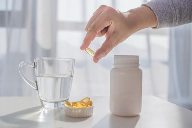 Mode de vie sain, médicaments, suppléments nutritionnels et concept de personnes - gros plan de mains mâles tenant des pilules avec des capsules d'huile de foie de morue et du verre à eau Photo gratuit