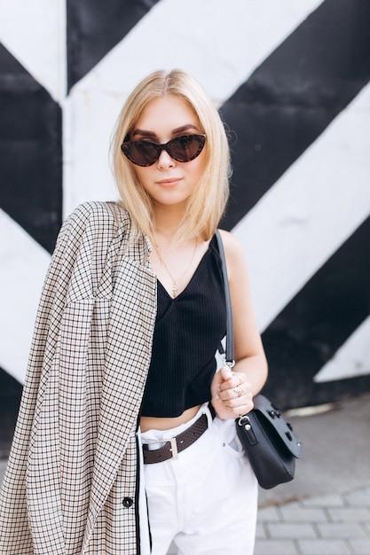 Mode de vie urbain mode portrait à la mode de la jolie jeune fille blonde vêtue de vêtements noir et blancs marchant dans la ville en jour d'été à lunettes de soleil Photo Premium