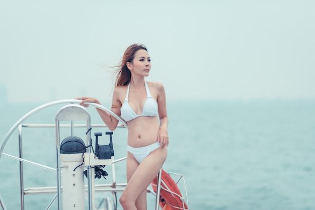 Modèle asiatique en bikini blanc sur un yacht Photo Premium