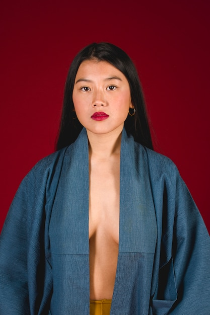 Modèle asiatique pose avec fond rouge Photo gratuit