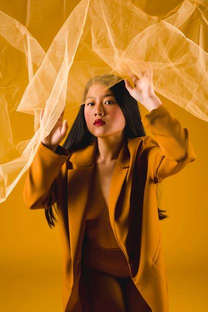 Modèle asiatique vue de face avec fond jaune Photo gratuit