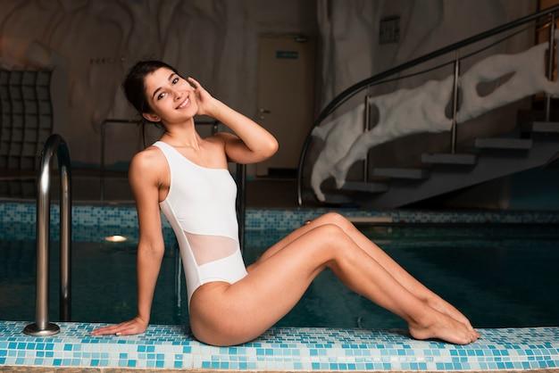 Modèle au spa posant à côté de la piscine Photo gratuit