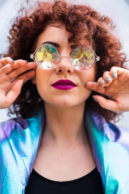 Modèle aux cheveux bouclés et lunettes Photo gratuit