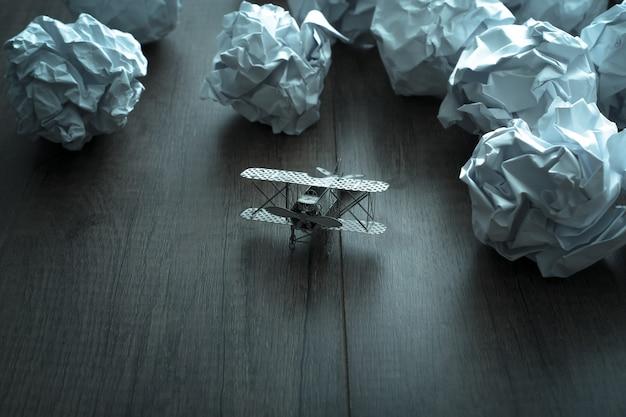 Modèle d'avion avec du papier froissé sur fond de bois. frustrations commerciales, stress au travail et échec à l'examen. Photo Premium